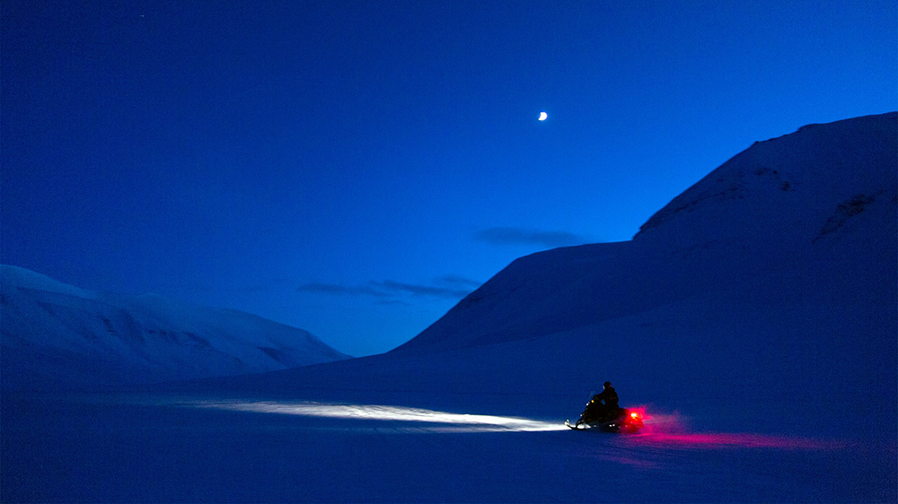 Snowscooter trip in the blue hours season